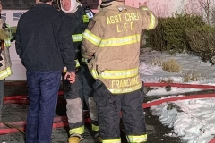 Chief Mullin and Asst. Chief Francione discuss operations with Firefighter Donavan after extinguishment